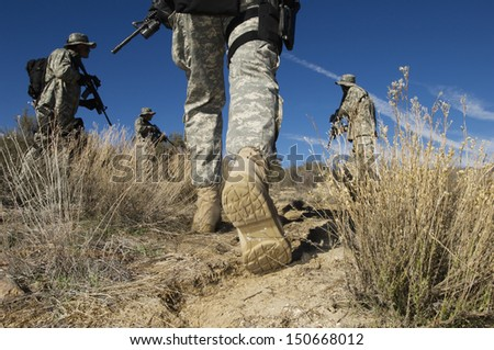 Soldiers walking in desert, low section - stock photo