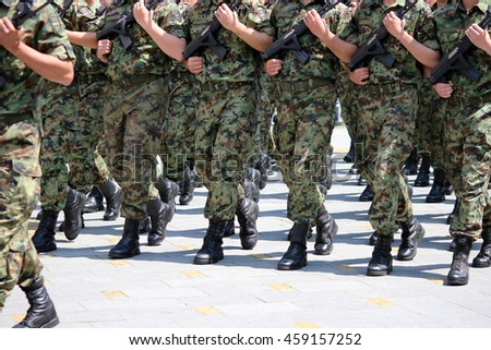 Soldiers with camouflage uniforms marching with rifles