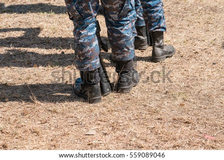 Soldiers with military camouflage uniform in army formation (military, army). soldier wearing camouflage uniform with gun - closeup on his leg and boot.