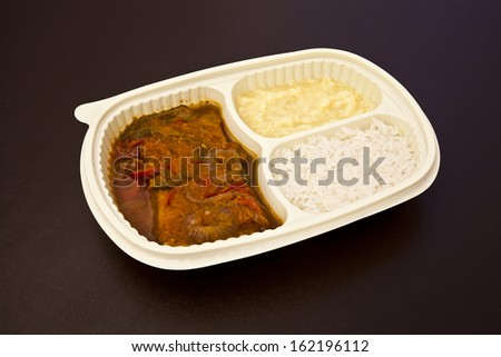 Sole with creole sauce and mashed potatoes in a package to go or to freeze. Package on brown leather background. - stock photo