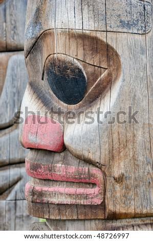 solemn face on totem - stock photo