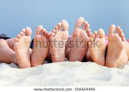 Soles of teenagers sunbathing on sandy beach - stock photo