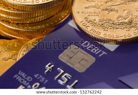 Solid gold coins contrasted with debit word on plastic credit card suggesting debt problems - stock photo