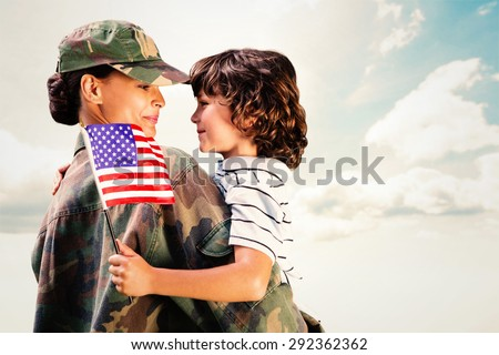 Solider reunited with son against blue sky - stock photo