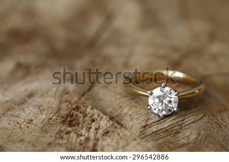 Solitaire engagement diamond ring won wooden organic background.  - stock photo