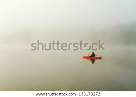 solitary fisherman in red kayak on a misty morning on a Missouri lake - stock photo