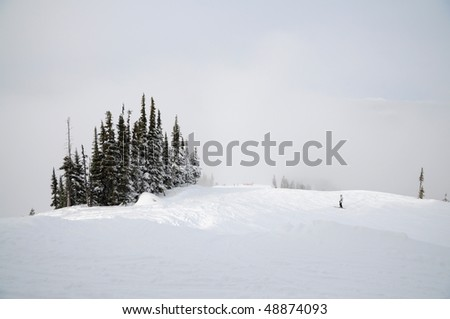 Solitary skier gliding up the slope on a cloudy hill - stock photo