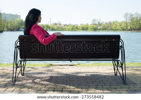 Solitude- Sad woman sitting on bench in park looking to the water - stock photo