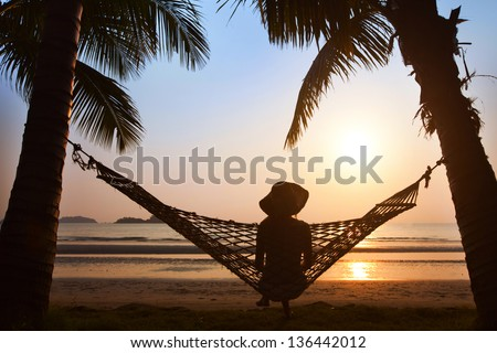 solitude, silhouette of woman in hat sitting alone  in hammock at sunset on the beach - stock photo