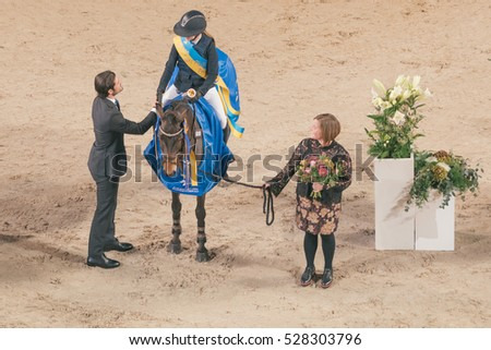 SOLNA, SWEDEN - NOV 26, 2016: Prize cermony with Prince Carl Philip in the pony jumping at the Sweden International Horse Show in Friends arena.