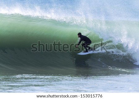 Solo surfer enjoying a fantastic morning of cold water winter surf, Quality waves. What every surfer dreams of. Location Kahutara, Kaikoura, New Zealand - stock photo