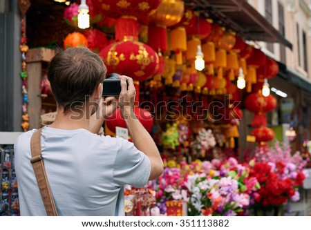 Solo traveler tourist taking photos of red colourful shop store decorations for chines new year in modern asian city - stock photo