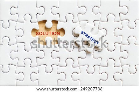 Solution and strategy words on jigsaw puzzle piece,business concept background