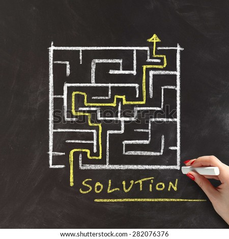 Solution or problem solving concept with a female hand drawing a maze or labyrinth on a blackboard with a yellow arrow marking the route through the puzzle - stock photo