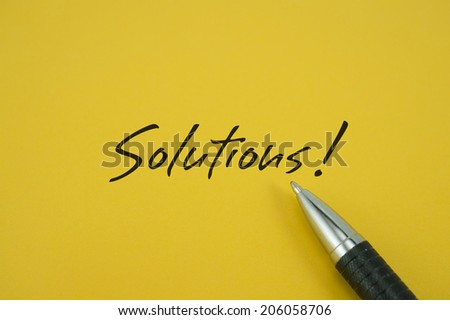 Solutions! note with pen on yellow background