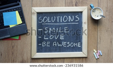 Solutions smile, love and be awesome written on a chalkboard at the office - stock photo