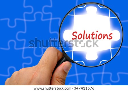 Solutions word. Magnifier and puzzles. - stock photo