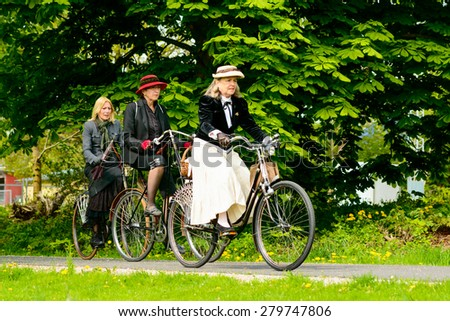 SOLVESBORG, SWEDEN - MAY 16, 2015: International Veteran Cycle Association (IVCA) 35th rally. Costume ride through public streets in town. Three women on old bikes.