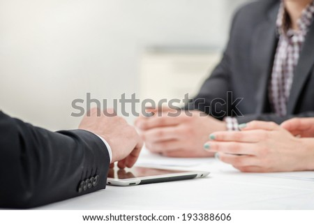 Solving problems! Hands of three and two businessmen discussing business affairs. Successful businessmen discussing business on a tablet. Couple man and woman sitting at the table. Close up arms - stock photo