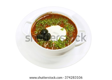 Solyanka soup in white bowl against white background. Described as a thick, spicy and sour soup in Ukrainian and Russian cuisine. Many variations, sometimes olives or lemon slices added, often salty.  - stock photo