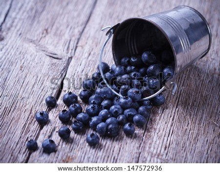 Some Blueberries in a small Bucket on wooden background  - stock photo