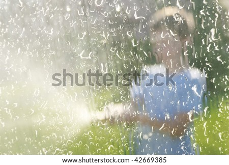some body is splattering water. water drops on the car's window. view from inside of the car. scratched and splashes pane - stock photo