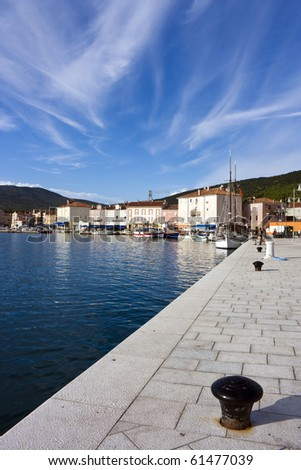 Some bollards and a sailing ship in harbor of cres on island cres in croatia - stock photo