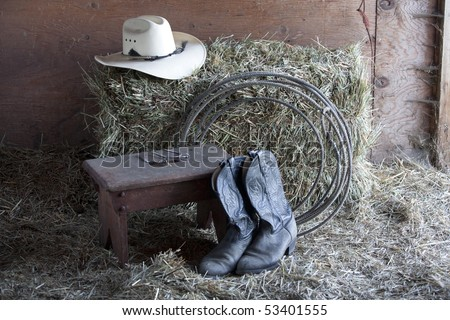 Some boots, a hat, a rope, and a bale of hay. - stock photo