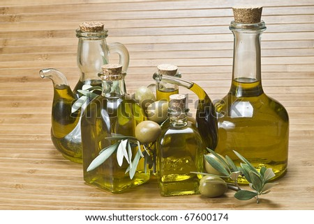 Some bottles with olive oil and some olives on a bamboo mat. - stock photo