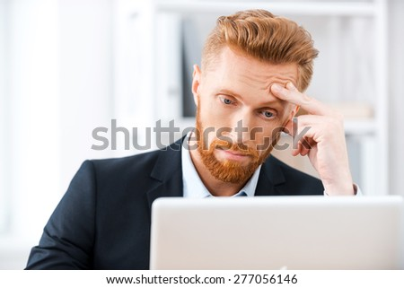 Some business troubles. Frustrated bearded businessman working on laptop and touching his head while sitting at his working place - stock photo