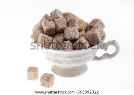 some cane sugar cubes in a small cup on white background. - stock photo