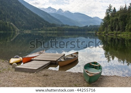 Some canoes ly on the shore of a quiet lake in the rocky mountains - stock photo