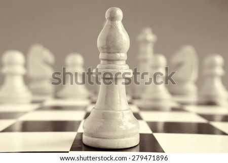 Some chess pieces on a chess board in a retro style.