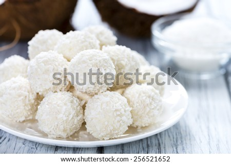 Some Coconut Pralines (close-up shot) on wooden background - stock photo
