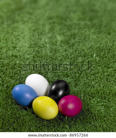some colored Easter eggs in green artificial grass background - stock photo