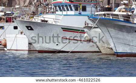 Some colorful fishing boats are anchored in the harbor of Acireale, Sicily-Italy on the coast of the Mediterranean Sea.