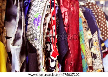 some different used clothes hanging on a rack in a flea market - stock photo