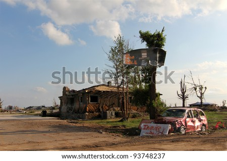 Some display a sense of humor in the midst of devastation such as the signs seen here.  Note the row boat deposited in the tree by a passing EF5 tornado. - stock photo