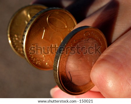 Some eurocoins between a woman fingers.