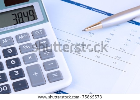 Some figures written in a paper. There is a ballpoint pen and a calculator in the scene. The photo have a deliberate blue photographic filter. - stock photo