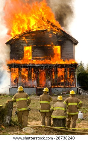 Some firemen stand in front of a house engulfed in flames