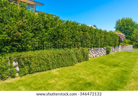 Some flowers and nicely trimmed bushes on the leveled and stoned front yard. Green fence. Landscape design. - stock photo