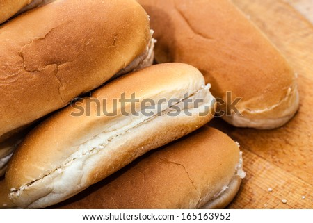 some fresh buns piled up on a wooden surface - stock photo
