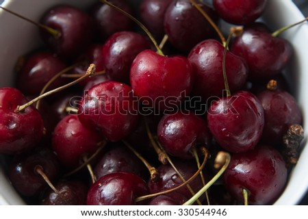 some fresh ripe red cherries on black table
