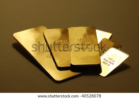 Some gold bars on a reflective surface - stock photo