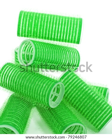 some green hair rollers on a white background