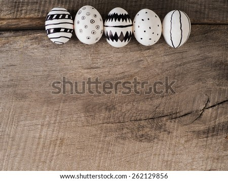 Some hand drawn easter eggs on a wooden table with copy space - stock photo