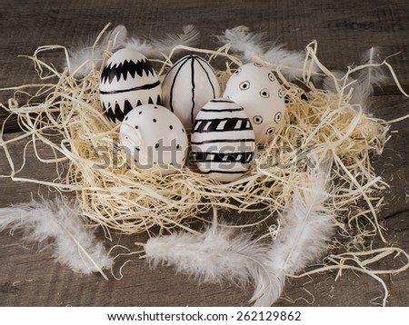 Some hand drawn easter eggs on a wooden table with white feather - stock photo