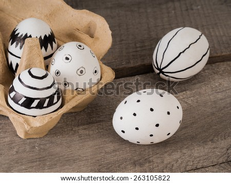 Some hand drawn easter eggs with black ink on a wooden table  - stock photo
