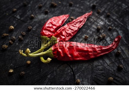 Some hot red peppers and black pepper lie on a dark board - stock photo